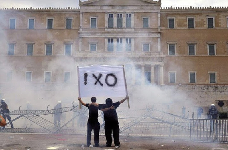 "Two anti-austerity protesters hold a ""NO"" banner in front of the Greek Parliament. Athens, 2011"
