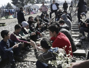 Refugees and immigrants holding flowers while participating in a protest at Idomeni, 1.3.2016. Photo: EFE