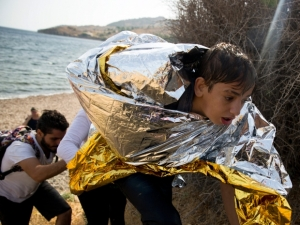 A young Syrian boy, wrapped with a thermal blanket, arrives on the Greek island of Lesbos on Monday with others after crossing aboard a dinghy from Turkey. (Petros Giannakouris/Associated Press)