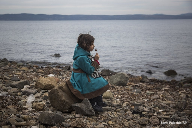 A Syrian girl eats a lollipop after her arrival on a boat from the Turkish coast to the Greek island of Lesbos. Photo: Santi Palacios