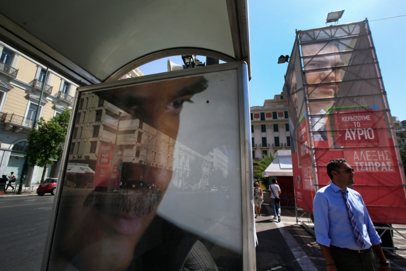 A man walks past a bus stop poster of Vangelis Meimarakis, left, leader of conservative New Democracy, backdropped by a banner, right, with a picture of Syriza leader Alexis Tsipras in central Athens, Wednesday, Sept. 16, 2015. (AP Photo/Lefteris Pitarakis) Source: www.neoskosmos.com